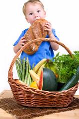 Kleiner Junge mit Picknickkorb isst Brot