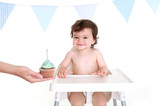 Baby with cup cake in highchair