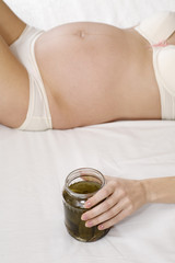 Pregnant woman holding jar of pickles