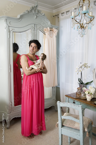 Drag queen wearing nightwear holding doll