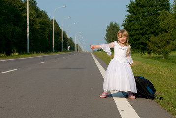 A girl with backpack on the road looking for car
