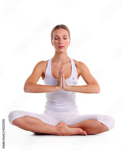Young woman practicing yoga, sitting in a lotus position