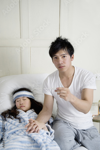Portrait of young man while woman lying in bed