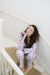 Young thoughtful woman sitting on stairway