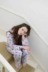 Sad young woman sitting on stairway in her pajamas