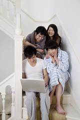 Young couples enjoying while using laptop