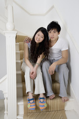 Full length portrait of young couple sitting on staircase