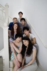 Group portrait of friends sitting in stairway