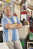 Portrait of smiling elderly man in automobile workshop