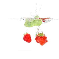 Erdbeeren mit Melisse fallen ins Wasser
