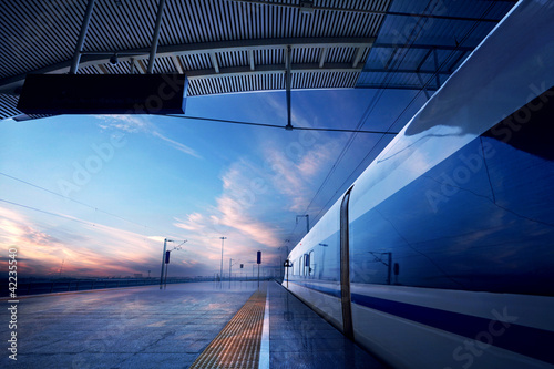 canvas print picture train stop at railway station with sunset