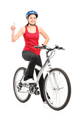 Female bicyclist posing on a bicycle and giving a thumb up