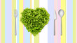 lettuce in the shape of heart on colored tablecloth with cutlery
