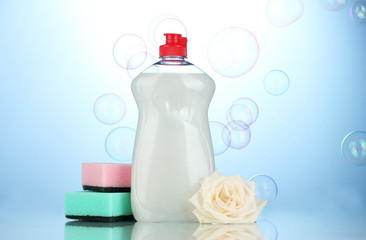 Dishwashing liquid with sponges and flower on blue background