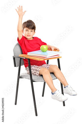 A schoolboy seated in a chair raising his hand