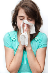 Sick teen girl using tissue. All on white background.