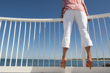 Sexy womans legs at ocean lookout background