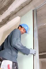 young black carpenter at work fixing door indoors