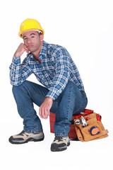 Bored builder sat on tool-box