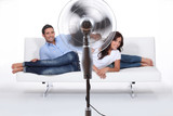 Man and woman laid on a sofa being ventilated by fan