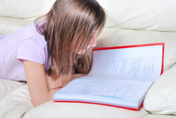 Girl student on the couch with a notebook