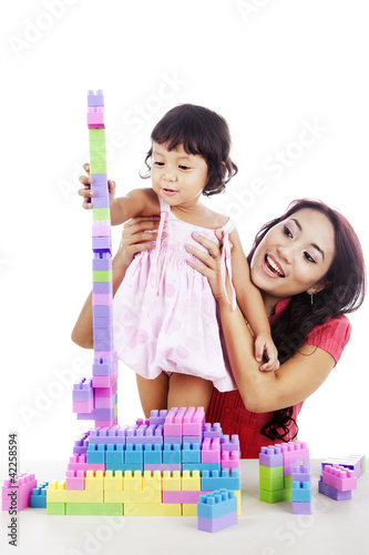 Girl with mother playing with blocks