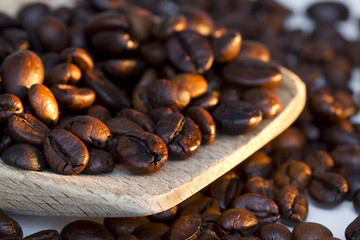 Coffee beans on wooden spoon and a white background