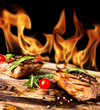 Grilled beef steaks with flames on background