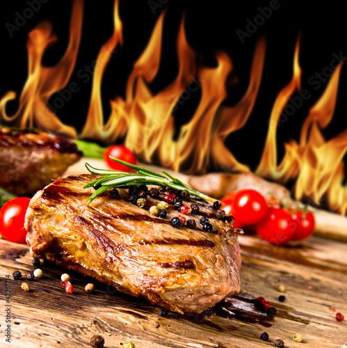 Gegrillte Rindersteaks mit Flammen im Hintergrund