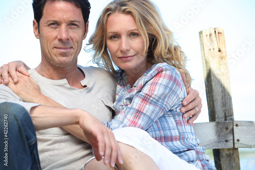Relaxed mature couple sitting in the sunshine