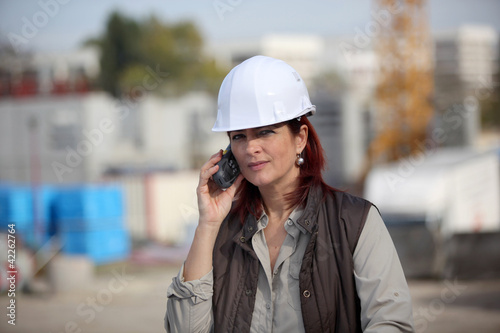 female architect making a call in construction site