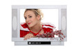Woman dressed in festive outfit coming out of television