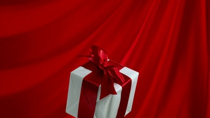 Gift box falling against red fabric, Slow Motion