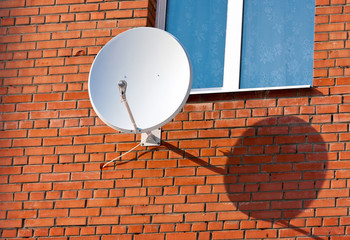 Satellite Dish mounted on  brick wall.