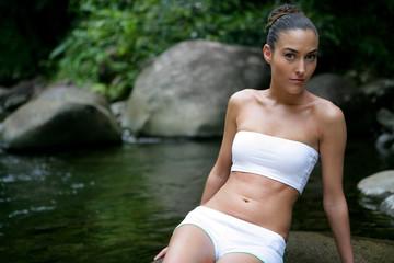 Brunette posing on rock in stream