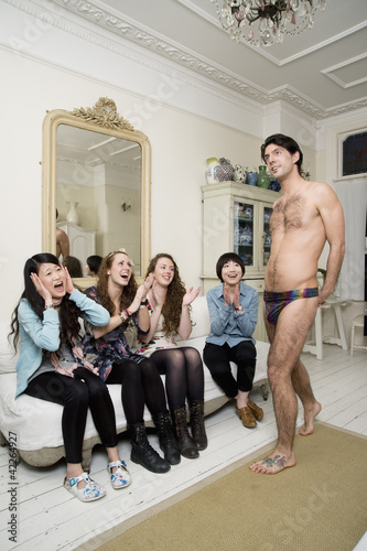 Male stripper posing in front of women