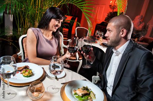 Piękna para z kieliszkami czerwonego wina w restauracji na roman