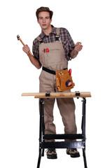 A tradesman standing behind a workbench