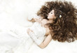 Dreaming bride with long curly hair lying down over white. Sleep