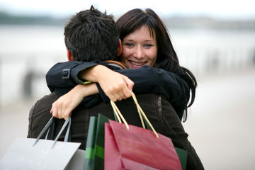 Woman thanking man for presents with hug