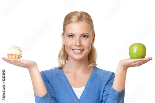 Attractive woman makes a tough choice between cake and apple