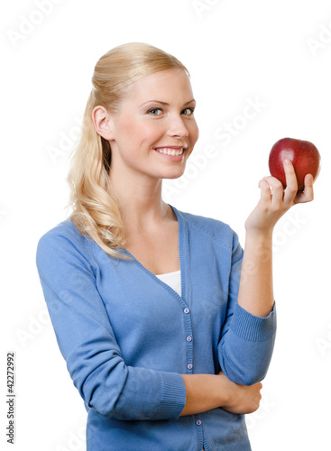 Smiling attractive woman offers a red apple, isolated