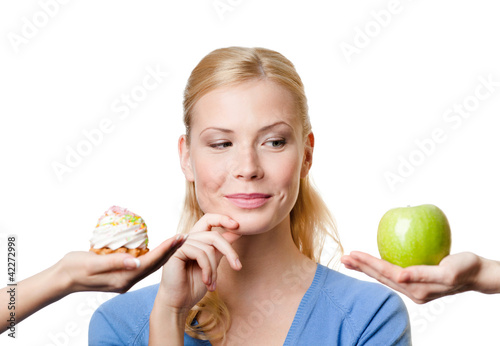 Beautiful woman makes a tough choice between cake and apple