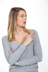 Astonished woman looking and pointing her finger sideways