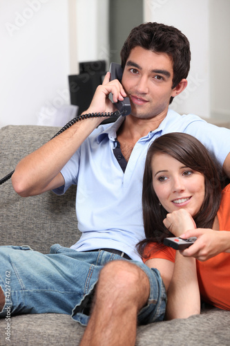 Young couple relaxing on the sofa and watching television
