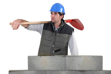 Man with spade stood by unfinished wall