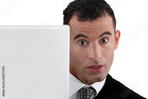 Surprised businessman at a laptop