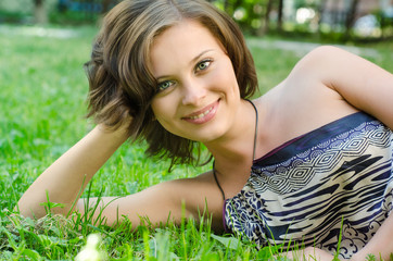 A beautiful young girl lying on the grass on a background of gre