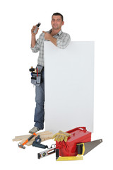 Carpenter pointing to mobile telephone