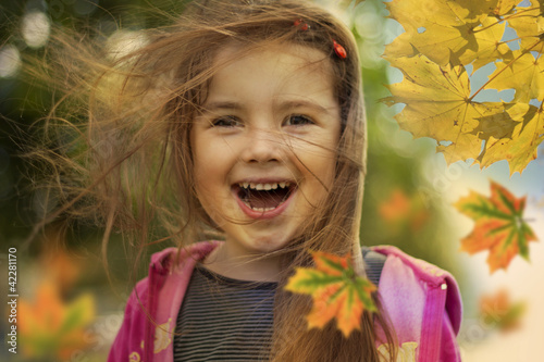 little girl in autumn with falling leaves and hair in wind